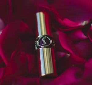 Un rouge à lèvres Yves Saint Laurent posé sur des pétales de rose.